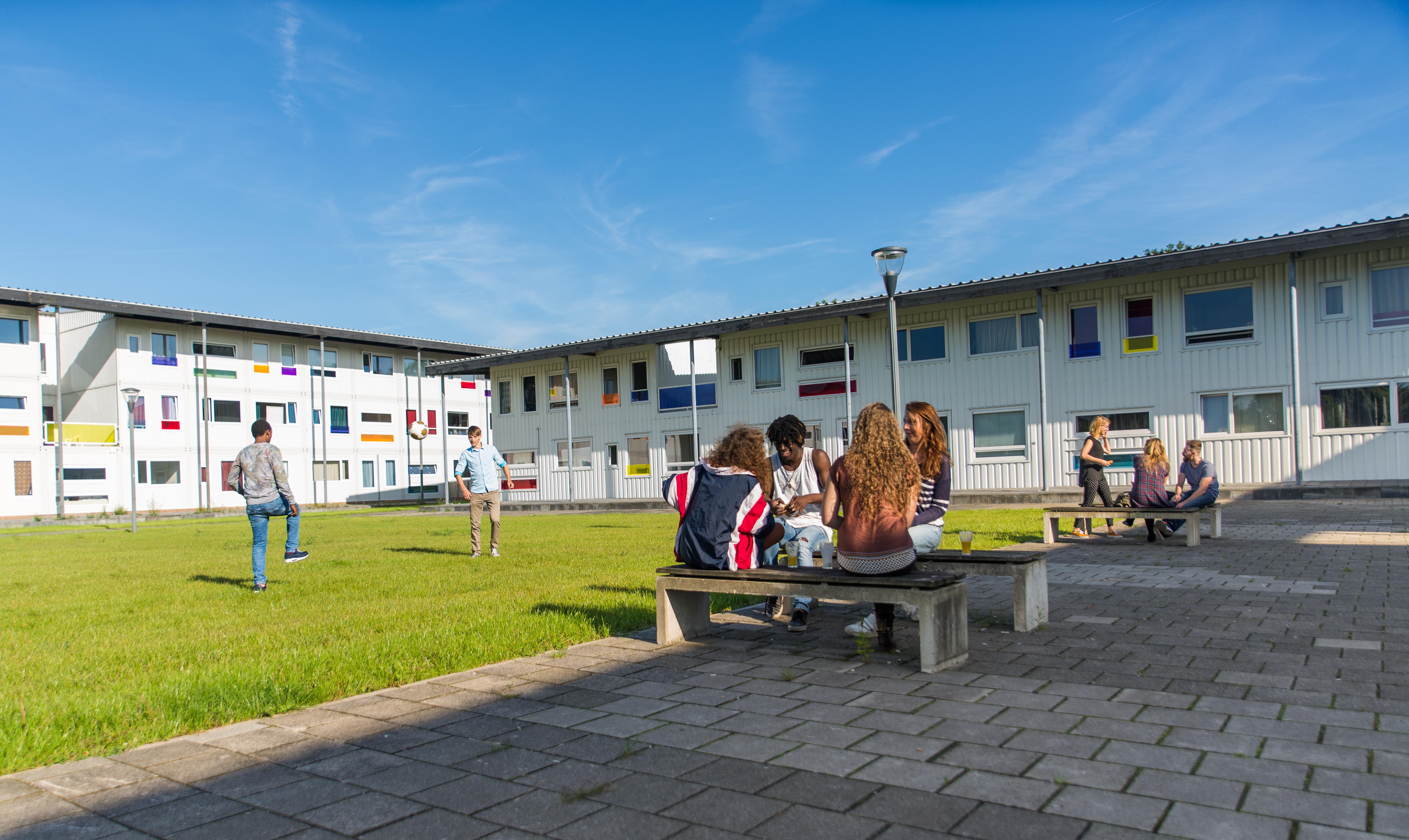 Foto na de oplevering van Startblok Riekerhaven met bewoners die aan het eten en voetballen zijn. Eenzelfde complex komt in Elzenhagen.
