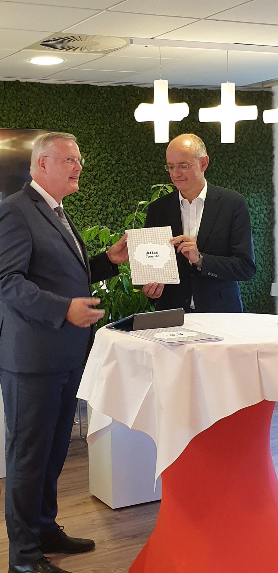 Onno van Veldhuizen, voorzitter van Regio Twente, ontvangt het allereerste exemplaar van de Atlas Twente van Andries Heidema, commissaris van de koning.