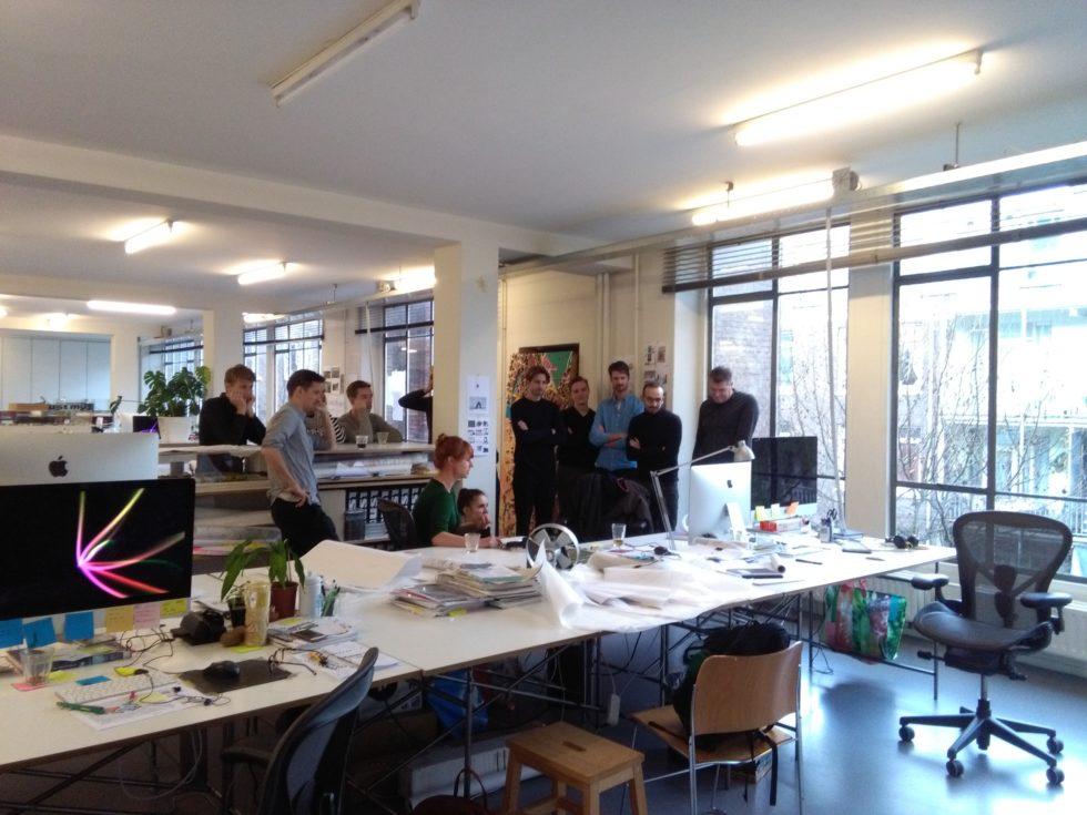 Foto van ons team die luister naar de maandagochtendpresentatie van Ziega